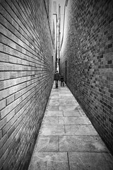 Two cousins in an alley (Christian Hacker) Tags: exeter alley streetphotography pointofview narrow brickwall boys cousins children blackandwhite bw mono monochrome close alleyway guildhall devon uk city street canon eos50d tamron 1750mm people kids parliamentstreet narroweststreetinuk pattern leadinglines lines bricks walls buildings architecture