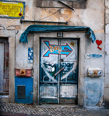 Lisbon Doorway (Greg Adams Photography) Tags: graffiti travel travels signs lisbon portugal europe street dor doorway paint colors color decay old worn arrow hhsc2000 heart cobblestones blue yellow red 2016