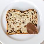 Kuchen mit gedörrten Früchten und Rosinen, an einer Ecke mit Schokolade-Nuss-Aufstrich thumbnail