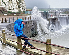 Catching a wave (Croydon Clicker) Tags: photographer camera filter cagoule anorak fence quay sea ocean wave splash breaker road cliff newhaven eastsussex sussex