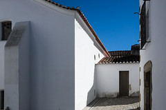 Evora, Portugal (Marian Pollock) Tags: evora architecture minimalist white buildings redroofs street shadows doors entrance bright portugal cobblestones rooftiles window sky shingles contrast europe town