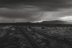 New Mex ([ raymond ]) Tags: clouds desert landscape mountains newmexico railroadtracks rain sky bnw blackandwhite virga