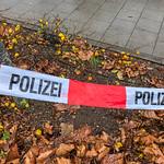 Polizei-Absperrband über kleiner Grünfläche vor Fussweg thumbnail