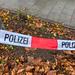 Polizei-Absperrband über kleiner Grünfläche vor Fussweg