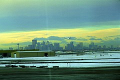 Downtown Calgary with Airport (pmvarsa) Tags: fall 2001 autumn analog film 135 agfa hdc 100iso agfahdc100 nikonsupercoolscan9000ed nikon coolscan cold snow winter sun set sunset tower downtown urban city airport airplane aeroplane skyline takeoff sky clouds canon ftb canonftb classic camera stop sign calgary alberta canada ab