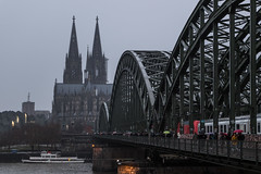 Cologne, Germany (Adrià Páez) Tags: cologne germany köln kölle north rhine westphalia deutschland europe river water cathedral church religion history historical catholic christian bridge hohenzollern architecture building boat train city sky people walking umbrellas