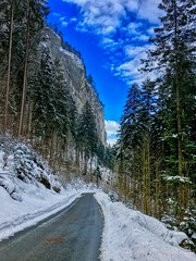 Steep cliffs of Kaiser mountains near Kufstein, Tyrol, Austria (UweBKK (α 77 on )) Tags: österreich steep cliffs mountain rock stone road street winter snow ice cold blue sky tree forest kaiser kufstein tyrol tirol austria europe europa iphone cliff