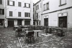 Outdoor tables (goodfella2459) Tags: nikonf4 afnikkor24mmf28dlens fujifilmneopanacros100 35mm blackandwhite film analog rimini italy tables buildings bwfp