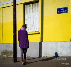 Street - Equality metaphysical (François Escriva) Tags: street streetphotography paris france people candid olympus omd photo rue woman colors sidewalk yellow purple name sign shutter égalité shadow shade alone standing up sweater white grey wall house building