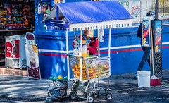 2018 - Mexico - Puebla - Fruit Basket (Ted's photos - Returns Saturday) Tags: cropped mexico nikon nikond750 nikonfx puebla tedmcgrath tedsphotos tedsphotosmexico vignetting oranges juice juicer blue broom cart shoppingcart streetscene street shadows pail bucket denimjeans denim curb sign cooler wheels