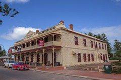 Franklin Harbour Hotel (Malcom Lang) Tags: hotel pub watering hole beer west end coopers windows doors pipes chimmney veranda balcony railing chairs tables road gutter trees branch cars bin sighns sky clouds cloud footpath stone coffee lightpole rocks water puddle pallet paving fence