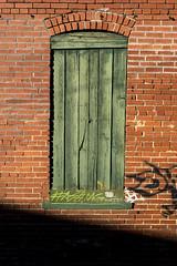 Brick Wall (DJ Wolfman) Tags: brick wall board green red grafitti shadow paint olympus olympusomd micro43 zuiko 12100mmf4zuiko zd wichitaks kansas old oldbuildings oldtown