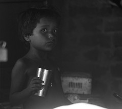 Eyes contact (ybiberman) Tags: varanasi india utterpradesh village children girl streetphotography candid nailpolish halfnaked dark bw drinking cup