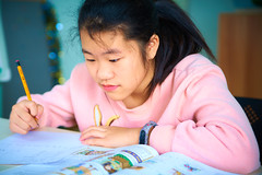 2019 Winter Camp Classroom Kids 15 (ArdieBeaPhotography) Tags: girl preteen pretty beautiful sweater top bunny ears pencil study learn textbook exercisebook writing printing bokeh background classroom inside desk table studious intent ponytail long black hair whiteboard tamronspaf2875mmf28xrdildasphericalif language english learning student young focused attentive