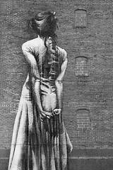 She Stands Tall (belleshaw) Tags: blackandwhite portland oregon streetart building mural woman dress bricks windows tall hair back arms hands figure detail