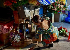Just After Sunrise:  Floral Vendor in a Floral Outfit (Ginger H Robinson) Tags: sunrise early morning opening market woman floral camouflage vendor flowers colorful sunlight benthanhmarket saigondistrict1 hcmc saigon vietnam southeastasia basket day new
