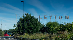 Leyton (M C Smith) Tags: pentax k3 leyton letters traffic bus red blue sky barrier black white lamps trees green bushes grass weeds lines clouds yellow sign arrow arrows