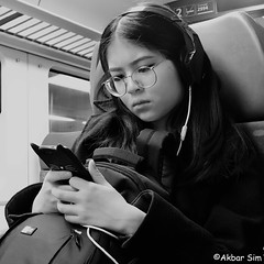 TRAVELLING BY TRAIN (Akbar Simonse) Tags: holland netherlands nederland trein train traveller reiziger girl woman bril spectacles phone smartphone people candid streetphotography streetshot straatfotografie straatfoto akbarsimonse bw blancoynegro bn monochrome zwartwit koptelefoon headphones rugzak backpack glasses