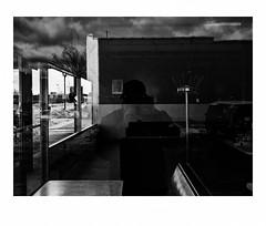 Coat rack in the Lincoln Park Cafe (Richard C. Johnson: AKA fishwrapcomix) Tags: panasonic lumixg9 20mmf17 blackandwhite bw monochrome restaurantwindow boothes chrome reflections selfportrait clouds trees shadows duluth minnesota winter sign decal smallbusiness lincolnpark supriorstreet modernity icamesofarforbeauty sictransitgloriamundi