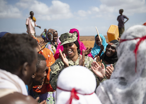 Navy Lt. Mellany George laughs as she dances with Djiboutian citizens.