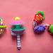 Set of plastic toys for newborn babies. Plastic rattle on the pink background. Flat lay photo.