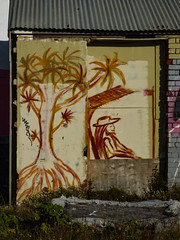Another Day in Paradise (Steve Taylor (Photography)) Tags: relaxing cabbagetree hat graffiti mural streetart chair seat brown smile smiling brick man newzealand nz southisland canterbury christchurch newbrighton tree sunny