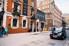 Great Scotland Yard (goodfella2459) Tags: nikonf4 afnikkor24mmf28dlens kodakektar100 35mm c41 film analog colour city london streets car pedestrians road taxi cab