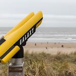 Fest installiertes Fernglas für den Blick über den Sandstrand von Zandvoort und den übergroßen Stuhl thumbnail
