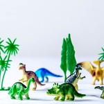 Group of toy plastic dinosaurs over white thumbnail