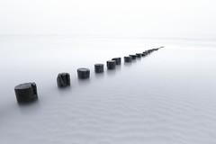 Milky sea breakers (Sander Grefte) Tags: westenschouwen sea poles zee palen mist mistig misty beach strand highkey landscape landschap sunset blackandwhite minimalistisch minimalism minimalistic le longexposure langebelichting