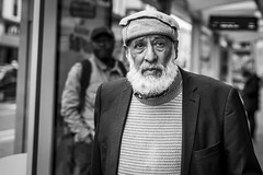 Tradition (Leanne Boulton) Tags: urban street candid portrait portraiture streetphotography candidstreetphotography candidportrait streetportrait eyecontact candideyecontact streetlife dutchangle leanneboulton old man male face eyes expression emotion mood feeling closeup hat traditional style fashion beard tone texture detail depthoffield bokeh naturallight outdoor light shade city scene human life living humanity society culture lifestyle people canon canon5dmkiii 70mm ef2470mmf28liiusm black white blackwhite bw mono blackandwhite monochrome glasgow scotland uk