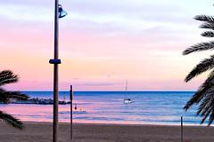Return at pink o'clock (Fnikos) Tags: sea water waterfront mar mare beach shore seashore sand coast sky cloud skyline tree palmtree boat sailboat blue pink people outdoor