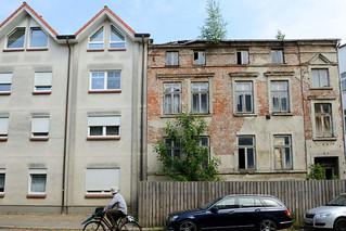 0-9852 Alt + Neu; ein Neubau mit schlichter grauer Fassade und Spitzdach steht neben der Hausruine eines verlassenen Wohngebäudes dessen Putz ab blättert und die roten Mauersteine zum Vorschein bringt; das Gebäude ist mit einem Bretterzaun abgesperrt.