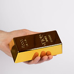 Hand holding a gold bar on white background thumbnail
