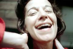 75-389 (ndpa / s. lundeen, archivist) Tags: nick dewolf nickdewolf color photographbynickdewolf 1975 1970s film 35mm 75 reel75 late1975 december winter boston massachusetts socialvisit friend friends woman brunette schenck sudieschenck face closeup smile smiling laugh laughter laughing socializing