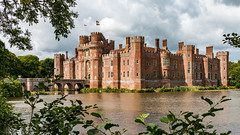 Herstmonceux Castle panorama (Keith now in Wiltshire) Tags: herstmonceux castle sussex brick wall tower turret battlement castellation chimney window flag bridge arch moat water tree foliage panorama building architecture fortress mansion sky cloud