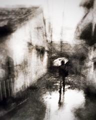 with rain comes the smell of asphalt . . . (YvonneRaulston) Tags: blur man figure impressionist moments moody texture wet monochromatic mono umbrella hoian vietnam rain