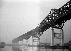 The Pulaski Skyway soars over burning junkyards and ancient industrial detritus in all of its hulking early 20th century mechanical glory. Jersey City. March 1975 (wavz13) Tags: oldphotographs oldphotos 1970sphotographs 1970sphotos oldphotography 1970sphotography oldhighways vintagehighways vintagephotographs vintagephotos vintagephotography filmphotos filmphotography oldhighway oldbridge oldbridges vintagehighway urbanwasteland industrialwasteland wasteland industry industrial bleak bleakwasteland brownfield brownfields vintagefactory oldfactory vintagefactories oldfactories vintageindustry oldindustry vintageindustrial oldindustrial vintagejerseycity oldjerseycity industrialjerseycity pollution polluted industrialbridge industrialbridges industrialage smokestack smokestacks newjerseyphotographs newjerseyphotos oldnewjersey vintagenewjersey newjerseyhistory vintagejerseycityphotography jerseycityhistory vintagebridges