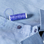 A spool of blue thread and needle on a man's shirt thumbnail