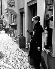 Shopkeeper (auqanaj) Tags: 02201920190309 kodakgold200 olympus35rc analog cewescanat72dpi film strase street strasenszene stadt cellphone mobile coat mantel smoke cigarette cobblestone brixen bressanone südtirol altoadige southtyrol break pause
