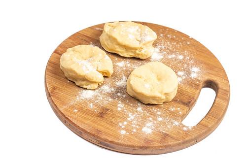 Raw Dough on the round wooden board