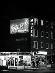 Big City Lights (Peter Glaab) Tags: hamburg neonleuchtreklame lettering hausfassade gebäude typografie nacht blackandwhite bierspezi motelhamburg hoheluftwest olympus zuiko 45mm radfahrer schlüsseldienst neon sign bewegungsunschärfe motion blur bikers