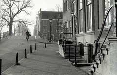 Amsterdam (angheloflores) Tags: amsterdam canal houses people street architecture urban explore city sunrise light black white ilford nikon fm2 holland wallpaper ilfordhp5 bnw amstel nederland