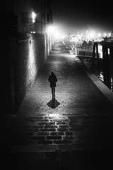 Venice nights (markfly1) Tags: venice italy fondamente nove woman walking along moonlit streets lamps silhouette shadow panama hat bright highlights dark shadows paving bricks stones textures shipyard lone person steps distance sea cityscape scene urban landscape mono black white image street candid photography nikon d750 50mm prime nikkor lens