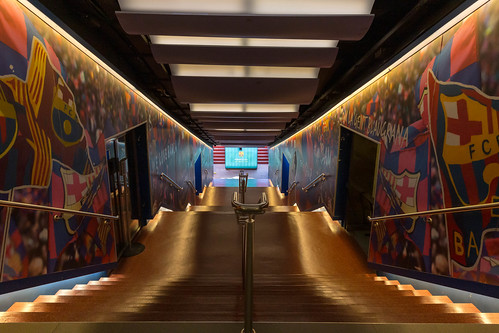 FC Barcelona players' tunnel leads to Camp Nou Stadium with painted club flags on the walls and illuminated stairway in Spain
