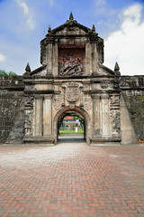 Main gate of Fort Santiago across its defensive moat. Intramuros-Manila-Philipines-0974 (rweisswald) Tags: intramuros manila fortsantiago matamoros saintjames moorslayer citadel gate gateway doorstep exterior southfront facade wood wooden sculpture intricatelycarved carving spanish coatofarms royalseal niche tunnel passage crossing fortification fortress defense curtainwall rampart castle military army stronghold garrison barracks quarter access entry vault vaulted arch buildingstone pavingstone redbrick block ashlar cobble cobblestone philippines