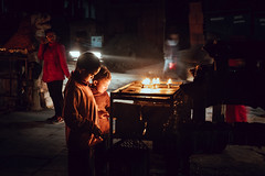 Brushing the Lamps (danielhibell) Tags: kathmandu nepal travel asia discover explore world street streetphotography people religion culture ambience mood buddhism hinduism colour light praying moving special