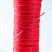 Coil of red thread with needle on white background