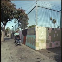 Klimt wall (ADMurr) Tags: la hollywood woman stroller sidewalk fence barb wire corner hasselblad 500cm 80mm zeiss planar kodak portra 160 film mf square dac2072