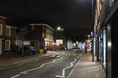 Night Shoot, 96 (doojohn701) Tags: street streetlighting architecture buildings sky dusk dark night windows shops car village glare shadow road lines crossing uk